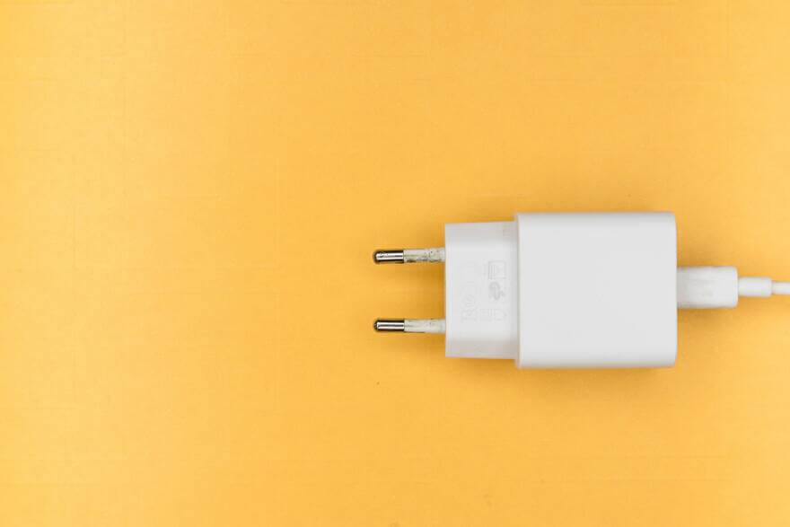 Chargeur de téléphone sur fond jaune.